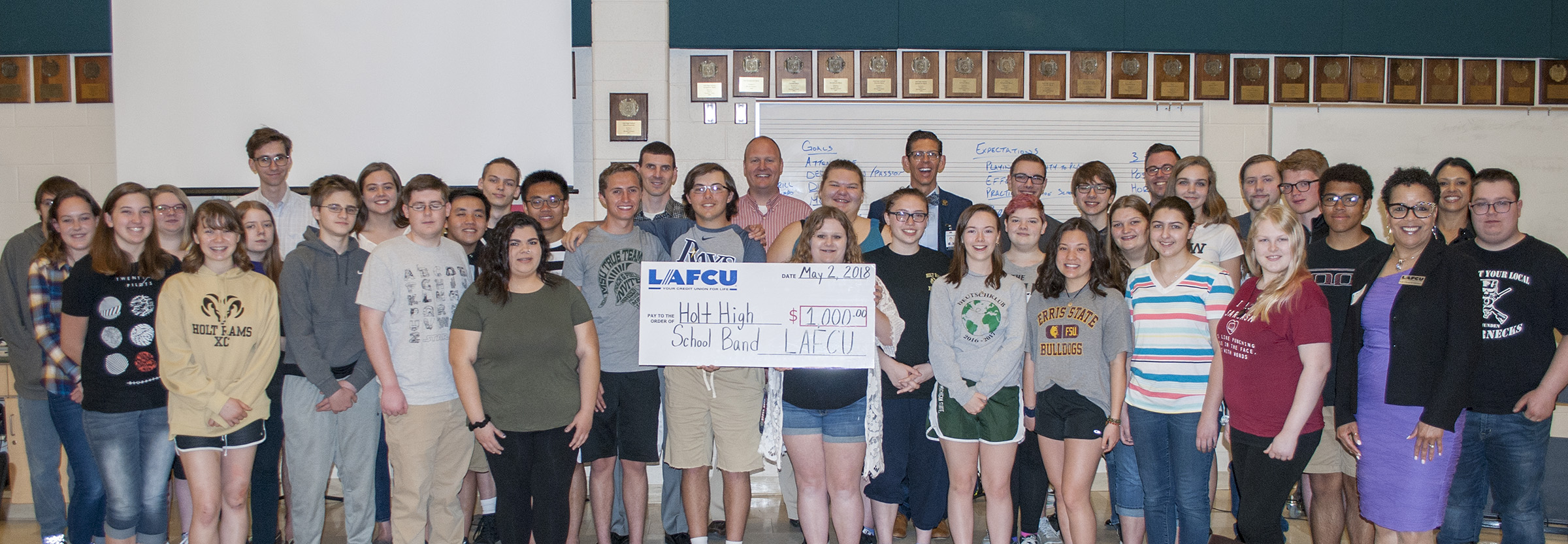 Some members of Holt High School's five bands accept the LAFCU donation on behalf of the school's band program. Also pictured are representatives of the school district, the high school, LAFCU and Lansing Regional Chamber of Commerce.