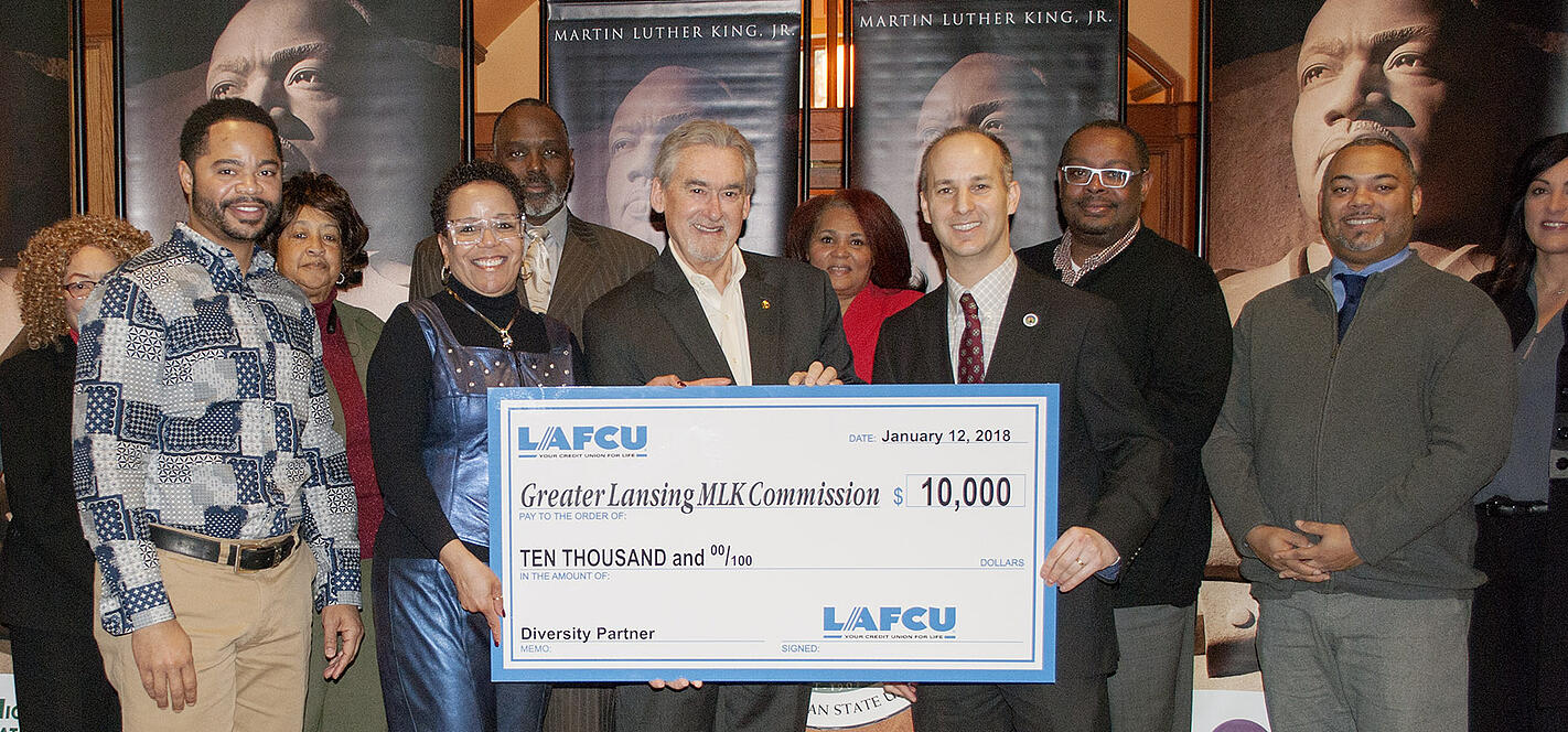 Surrounded by commissioners for the Greater Lansing Area Dr. Martin Luther King Jr. Holiday Commission, Kelli Ellsworth Etchison with LAFCU presents a ceremonial check to the mayors of East Lansing, Mark Meadows, center, and Lansing, Andy Schor. Both cities are Commission partners.