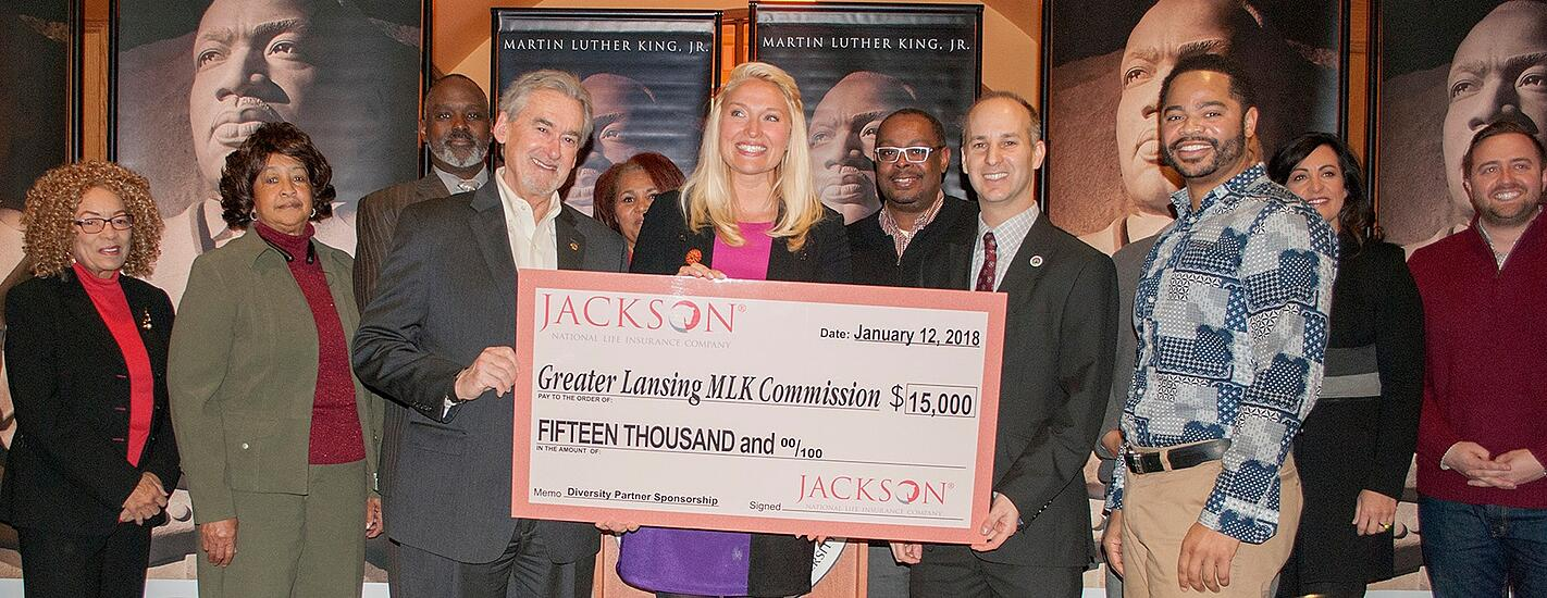 Danielle Robinson from Jackson National Life, center, presents a ceremonial check to the Commission. Also holding the check are Mark Meadows, East Lansing mayor, left, and  Andy Schor, Lansing mayor. The cities of East Lansing and Lansing are Commission partners.