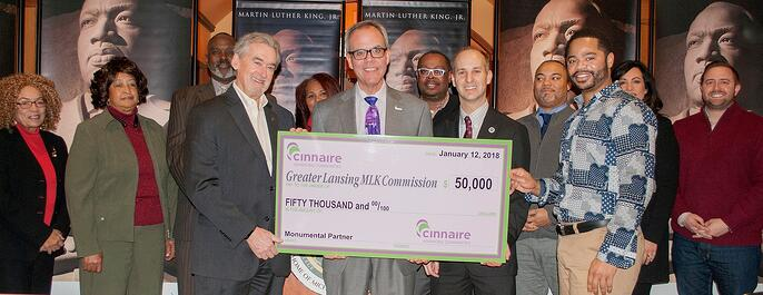 Mark McDaniel with Cinnaire, center, presents a ceremonial check to the Commission. Also holding the check are Mark Meadows, East Lansing mayor, left, and Andy Schor, Lansing mayor. The cities of East Lansing and Lansing are Commission partners.