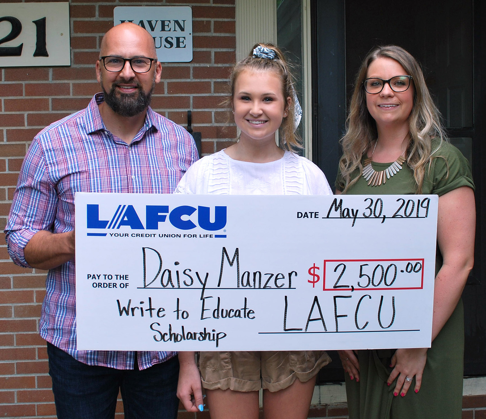 LCC-bound Daisy Manzer, center, receives the LAFCU Write to Educate scholarship from LAFCU Marketing and Communications Specialist Alyssa Sliger, at right. Also pictured is Manzer's father, Brandon Manzer of DeWitt.